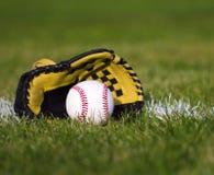 在黄色手套的棒球在与调车场界线和草的领域 免版税库存图片