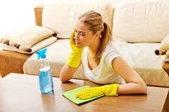 在黄色手套的疲乏的少妇清洁桌 免版税库存图片