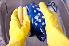 在黄色手套的洗涤的盘 库存照片