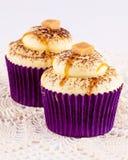 在紫色文件的两块焦糖杯形蛋糕 免版税库存图片