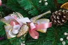 在绿色新年树枝的圣诞节桃红色丝带 库存图片