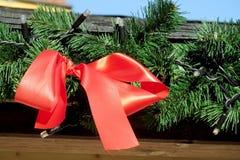 在绿色新年树枝的圣诞节红色弓 免版税库存照片