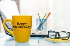 在黄色早晨咖啡杯的愉快的星期三词在被弄脏的家或办公室背景 免版税库存照片