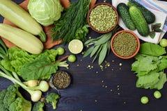 在绿色有机素食产品黑暗的背景的构成:绿叶蔬菜,绿豆,夏南瓜,大蒜,葱 库存照片