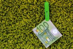 在绿色服装扣子的绿色钞票100欧元在绿色背景 库存图片