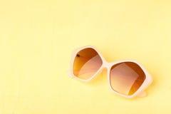 在黄色木桌上的太阳镜 图库摄影