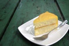 在绿色木桌上的橙色蛋糕 图库摄影