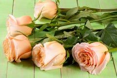 在绿色木背景的五朵新鲜的米黄玫瑰 免版税图库摄影