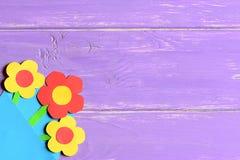 在紫色木背景的五颜六色的纸花与拷贝倒空文本的空间 花卉明亮的看板卡 免版税图库摄影