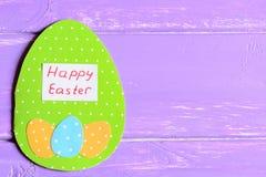 在紫色木背景的愉快的复活节贺卡与文本的拷贝空间 库存图片