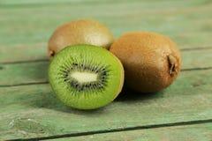 在绿色木背景的猕猴桃 免版税图库摄影