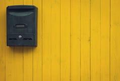 在黄色木背景的老邮箱 库存图片