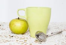 在绿色杯子和苹果的热的茶 库存图片
