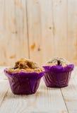 在紫色杯子的两个新近地被烘烤的松饼 库存图片