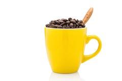 在黄色杯子的充分的咖啡豆 免版税图库摄影
