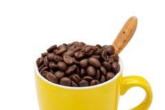 在黄色杯子的充分的咖啡豆 免版税库存图片