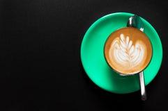 在绿色杯子的热的拿铁有在泡沫顶视图的花卉样式的在黑暗 免版税库存图片