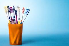 在黄色杯子的牙刷在明亮的蓝色背景 库存照片