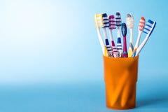 在黄色杯子的牙刷在明亮的蓝色背景 免版税库存照片