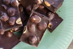 在绿色板材的巧克力和坚果大块 免版税库存照片