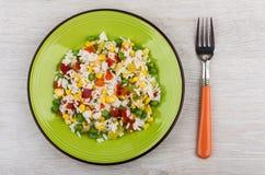 在绿色板材的菜与红色把柄的混合和叉子 免版税图库摄影