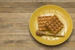 在黄色板材的维也纳奶蛋烘饼用蜂蜜 库存照片
