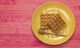 在黄色板材的维也纳奶蛋烘饼用蜂蜜 免版税库存照片