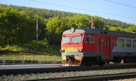 在绿色树背景的红色火车  免版税库存照片