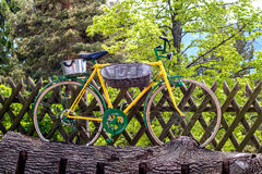 在绿色树背景的黄色自行车 免版税库存照片