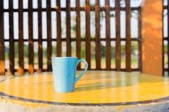 在黄色桌,咖啡杯正面图上的蓝色杯子 免版税库存图片