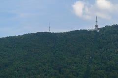 在绿色森林小山顶部的通讯台 免版税库存图片