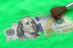 在绿色沙子的一百美元 免版税库存照片