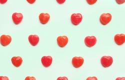 在绿色淡色纸的颜色背景的红色华伦泰` s天心脏糖果样式 概念亲吻妇女的爱人 五颜六色的行家样式 顶视图 库存图片
