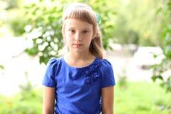 在绿色灌木中的小女孩蓝色礼服明亮的晴朗的夏日公园,看青少年的时尚样式的想法概念 图库摄影