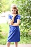 在绿色灌木中的小女孩蓝色礼服明亮的晴朗的夏日公园,看青少年的时尚样式的想法概念 免版税图库摄影