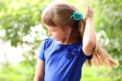 在绿色灌木中的小女孩蓝色礼服明亮的晴朗的夏日公园,看青少年的时尚样式的想法概念 库存图片