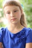 在绿色灌木中的小女孩蓝色礼服明亮的晴朗的夏日公园,看青少年的时尚样式的想法概念 免版税库存照片
