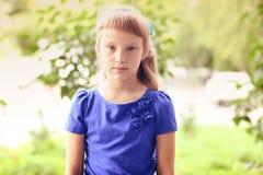 在绿色灌木中的小女孩蓝色礼服明亮的晴朗的夏日公园,看青少年的时尚样式的想法概念 免版税库存图片