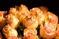 在黄色玫瑰的婚戒 免版税库存图片