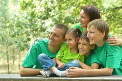 在绿色球衣休息的家庭 免版税库存图片