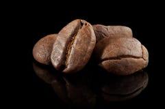 在黑色的一些咖啡豆 免版税图库摄影