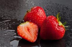 在黑色的三个草莓与水下落 免版税库存图片