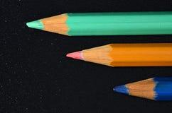 在黑色的三只蜡笔 免版税库存图片
