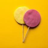 在黄色的两个棒棒糖 免版税库存图片