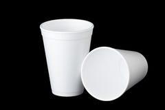 在黑色的两个聚苯乙烯泡沫塑料杯子 免版税库存照片