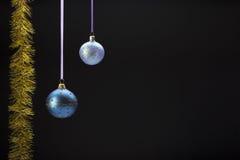 在黑色的垂悬的五颜六色的圣诞节球 免版税库存照片
