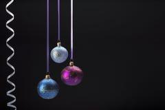 在黑色的垂悬的五颜六色的圣诞节球 免版税库存图片