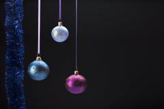 在黑色的垂悬的五颜六色的圣诞节球 库存图片