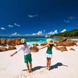 在绿色的夫妇获得在海滩的乐趣在塞舌尔群岛 免版税图库摄影