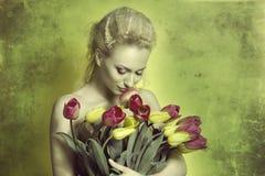 在绿色的女孩嗅到的郁金香 库存图片